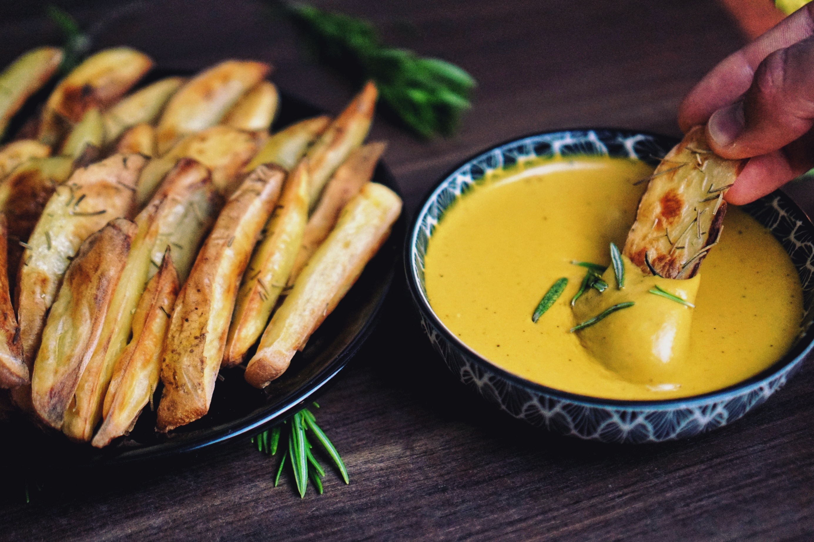 "Gebackene Kartoffeln gedippt in Cashew ""Käse"" Soße mit Rosmarin."