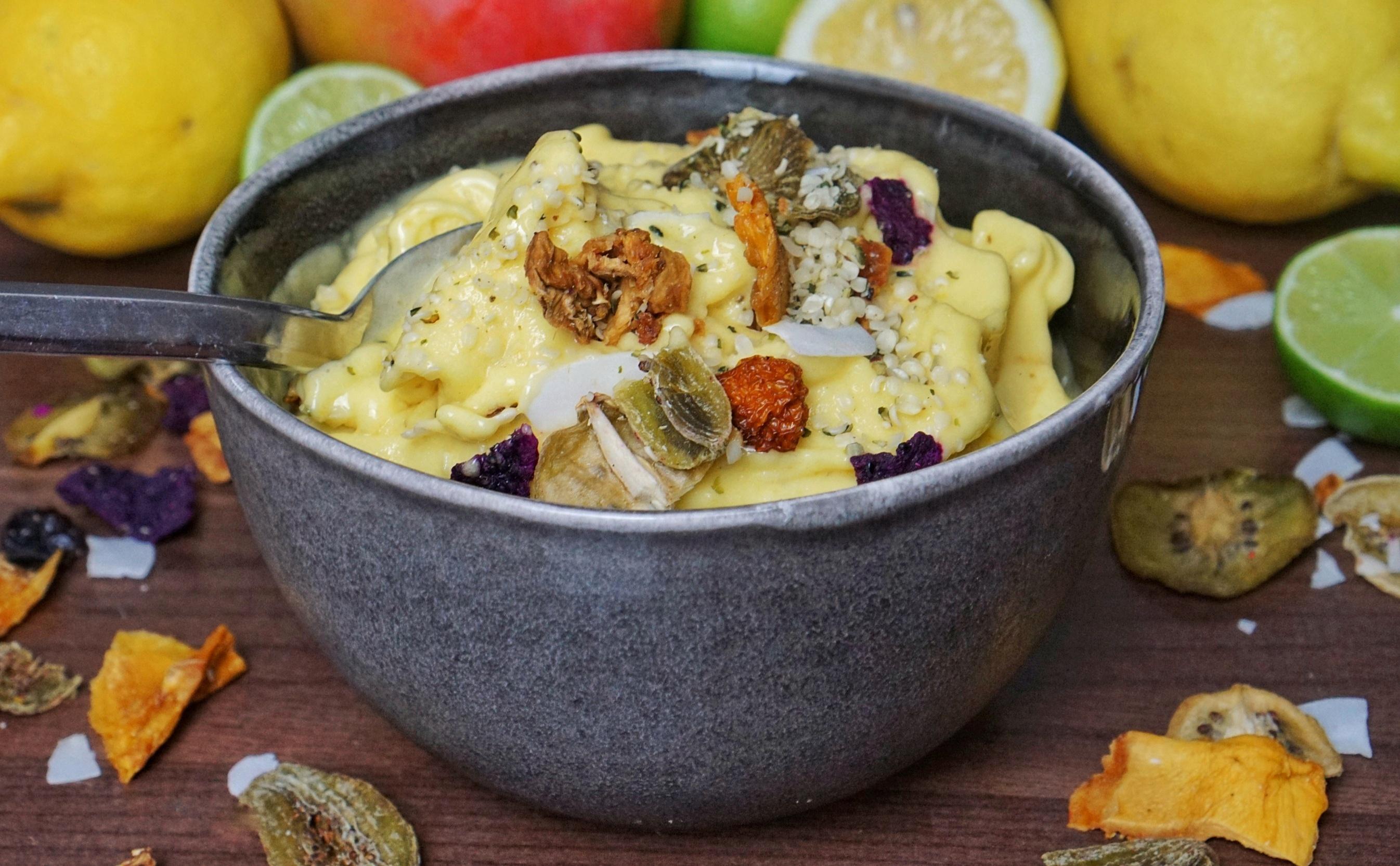Schale mit Löffel und Bananen Mango Eis mit getrocknetem Früchte Mix.