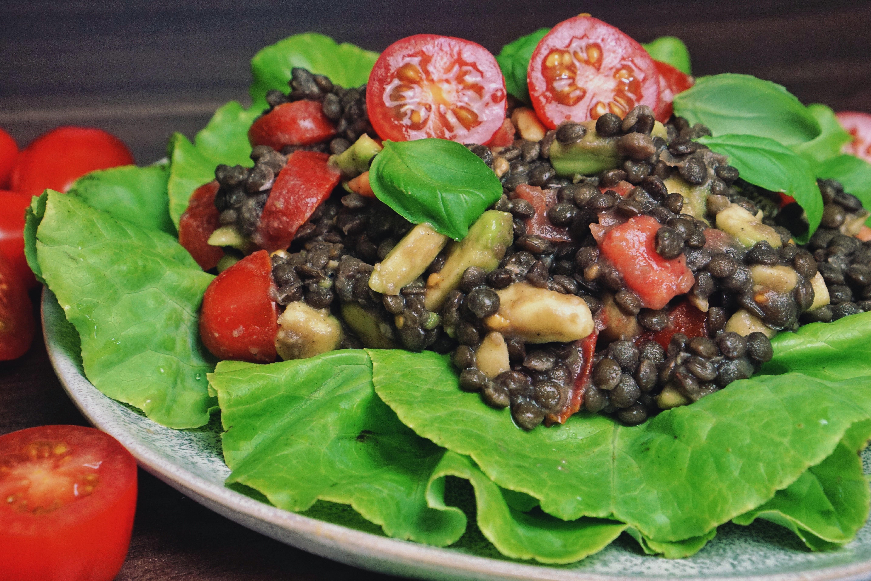 Beluga Linsen Salat mit Tomate und Avocado auf Blattsalat.