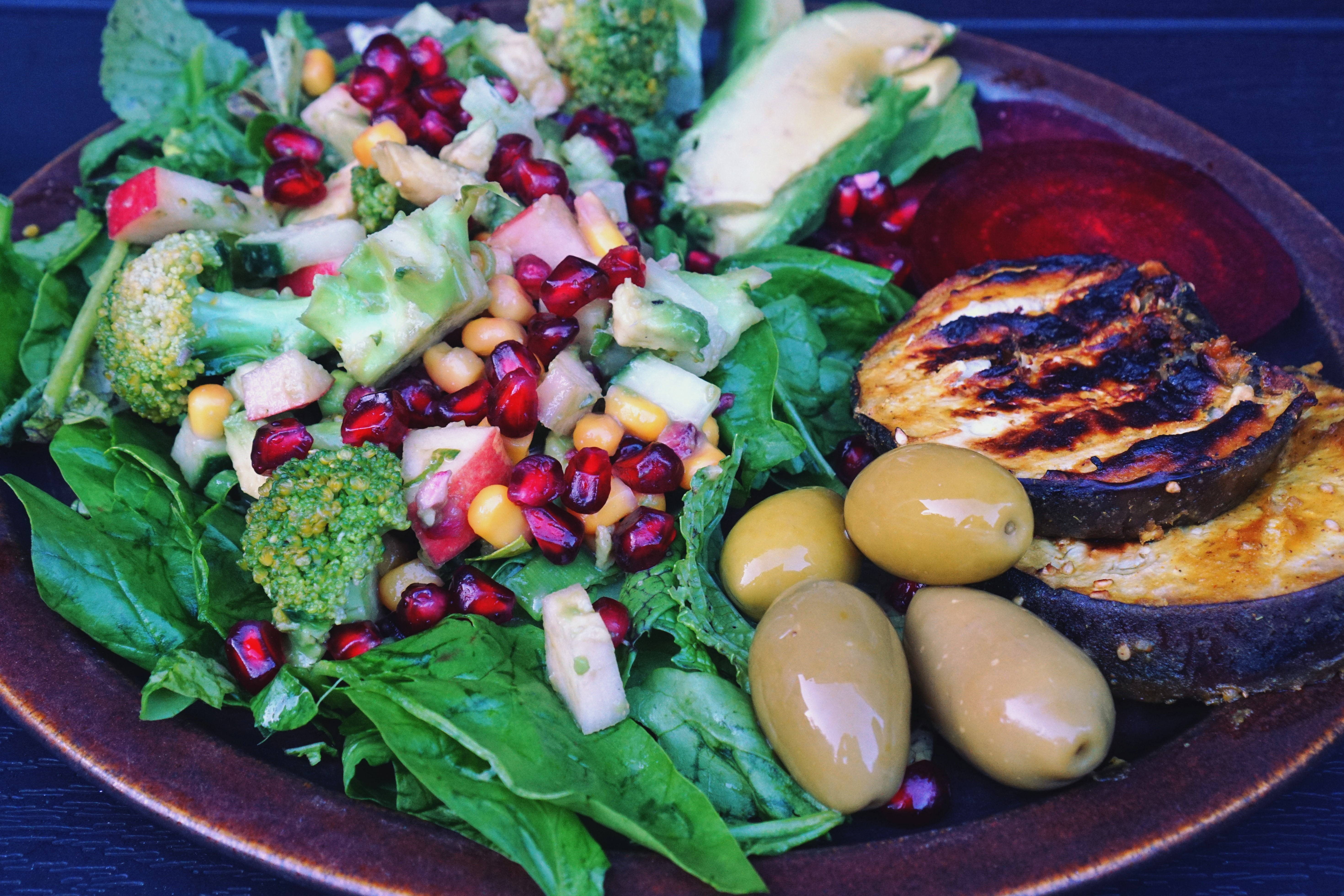 Teller mit buntem Brokkoli Salat, Oliven, gegrillter Aubergine, roter Beete und Avocado.