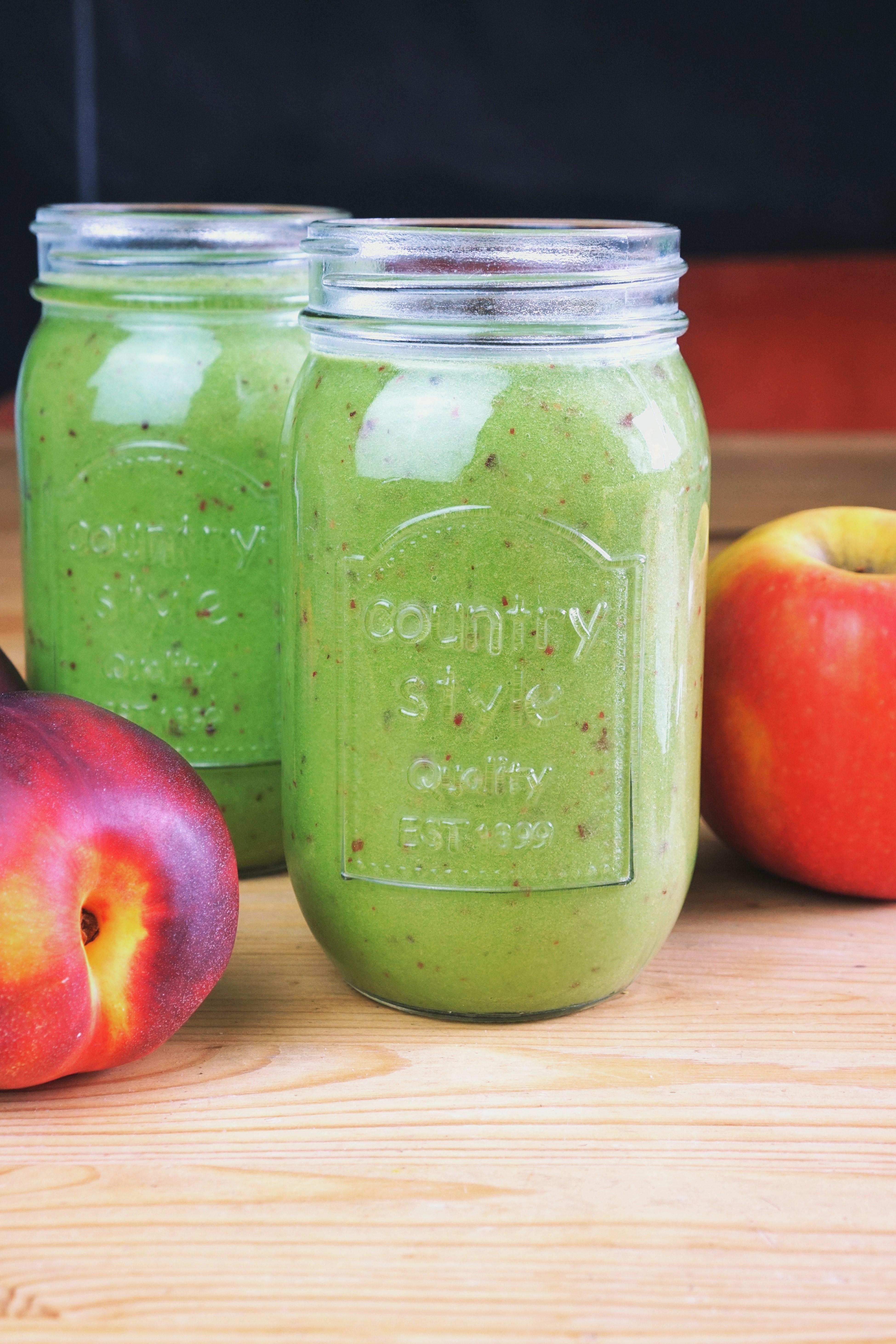 2 grüne Smoothies im Glas neben Nektarinen und einem Apfel.