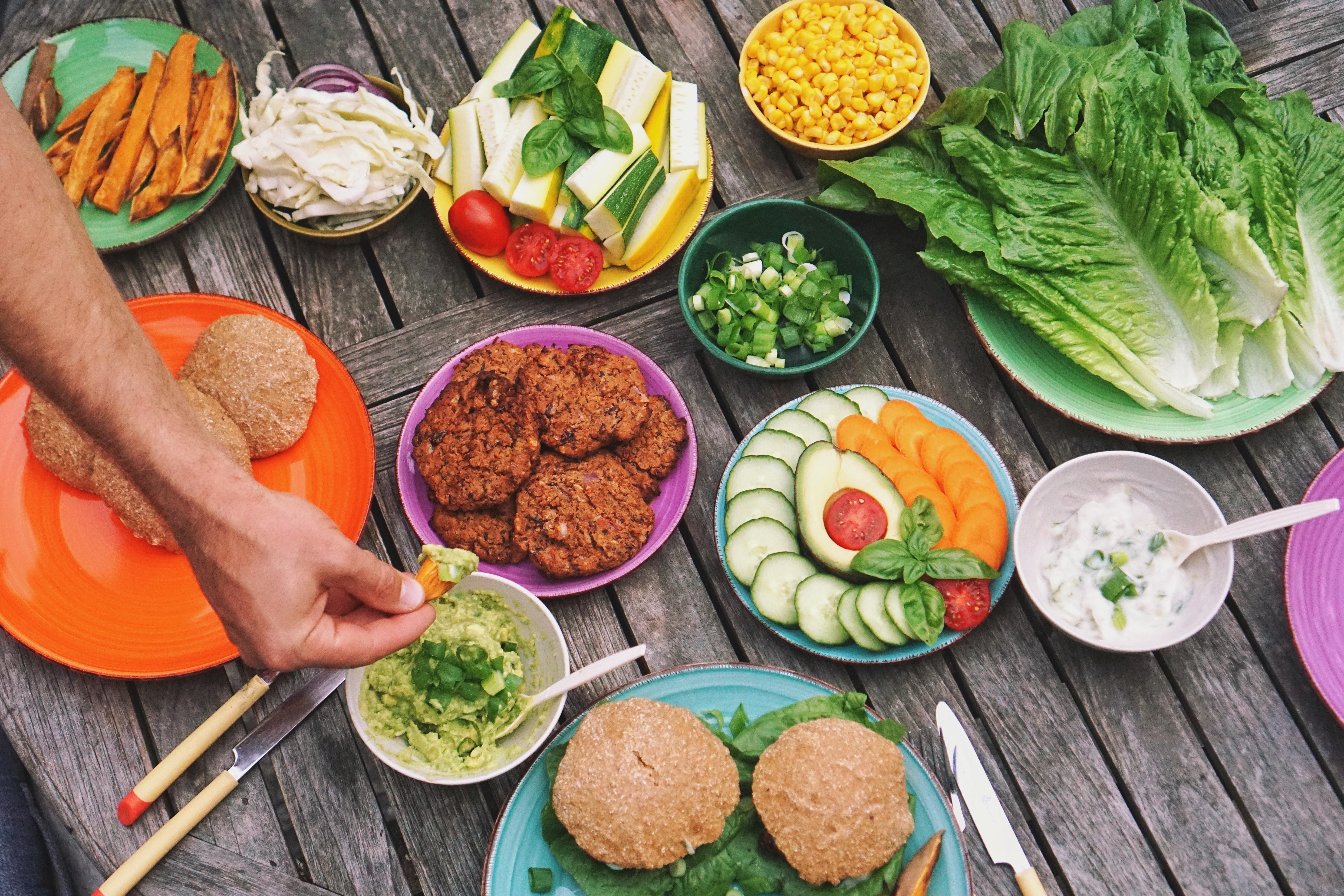 bunte Teller mit Gemüse und Salat und dazu Burger Brötchen und Burger.